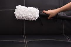 从在黑皮革长沙发使用的蒸气清洁法机器的白色织品刷子 免版税图库摄影
