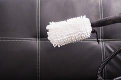 从在黑皮革长沙发使用的蒸气清洁法机器的白色织品刷子 图库摄影