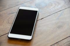 在黑盒的白色巧妙的电话在木桌上为m做准备 免版税图库摄影