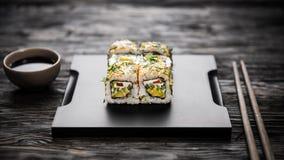 在黑盘子的菜寿司卷用大豆和筷子 免版税库存图片