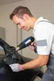 在黏着性箔或影片包裹的汽车镜子乘包裹专家的汽车 免版税库存照片