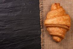 在黑石背景的一个新月形面包与您的文本的拷贝空间 顶视图 库存图片