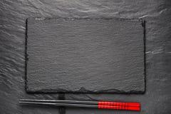 在黑石背景的两双筷子与copyspace 免版税库存图片