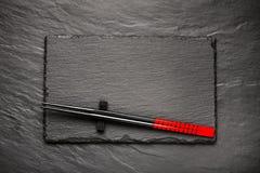 在黑石背景的两双筷子与copyspace 免版税库存照片