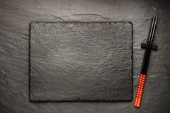 在黑石背景的两双筷子 免版税图库摄影