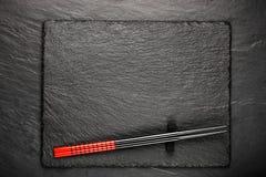 在黑石背景的两双筷子 库存图片