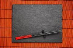 在黑石背景的两双筷子 免版税库存图片