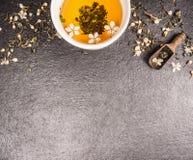 在黑石背景的茉莉花茶与鲜花和杯子,顶视图 免版税库存图片