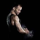 在滑石,黑背景的男性powerlifter手 免版税库存照片