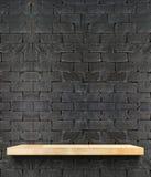 在黑砖墙,模板嘲笑的空的木架子为disp 库存图片