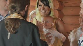在洗礼期间,礼拜式孩子微笑给教士 股票视频