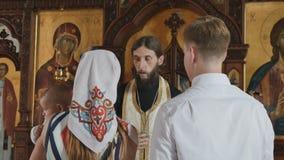 在洗礼期间,仪式教士背诵用父母的祷告有婴孩的 股票视频