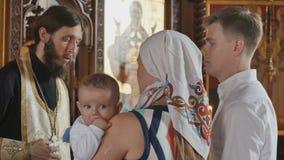 在洗礼期间,仪式有小儿子的父母听着教士 股票录像