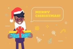 在给礼物的圣诞老人帽子的黑商人 库存图片