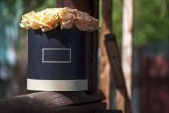 在黑礼物盒的美丽的乳脂状的玫瑰 免版税库存图片