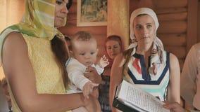 在洗礼仪式期间,教母拿着胳膊的一个小男孩 股票录像