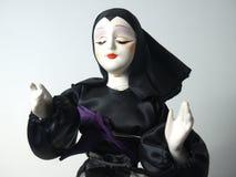 在给祝福的黑习性的玩偶 库存照片