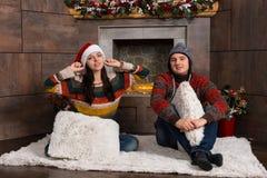 在滑稽的冬天帽子的年轻夫妇坐在t前面的一个地毯 库存图片