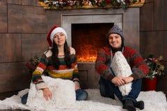 在滑稽的冬天帽子的年轻微笑的夫妇坐一个地毯在fr 免版税库存照片