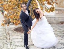 在滑稽的姿势的笑的婚礼夫妇 免版税库存图片