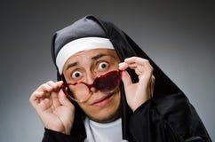 在滑稽的概念的人佩带的尼姑衣物 免版税图库摄影