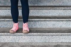 在黑站立在步的绑腿和桃红色运动鞋的妇女腿 免版税库存图片