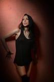 在黑站立在砖红色背景的T恤杉和长的长袜的有吸引力的长的黑发模型 纵向肉欲的妇女 库存图片