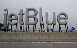 在终端5的JetBlue标志在约翰・肯尼迪国际机场在纽约 免版税库存照片