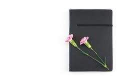 在黑笔记本的桃红色康乃馨花 免版税库存照片