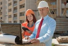 在建筑工地前面的二个建筑师工作 免版税库存照片