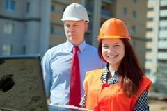 在建筑工地前面的二个建筑师工作 免版税库存图片