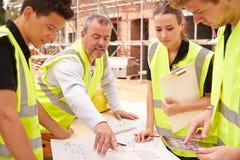 在建筑工地的建造者谈论工作与学徒 图库摄影