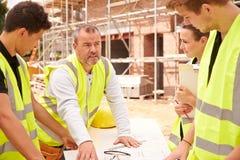 在建筑工地的建造者谈论工作与学徒 免版税图库摄影