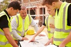 在建筑工地的建造者谈论工作与学徒 库存照片