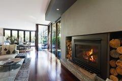 在建筑师的舒适圆木状燃烧嘴火设计了现代房子 库存照片