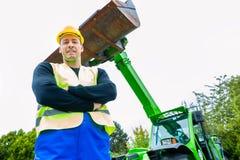 在建筑机械前面的建造者 免版税库存照片
