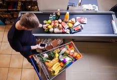 在结算离开前的人在超级市场 免版税库存照片