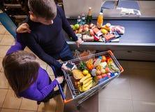 在结算离开前的夫妇在超级市场 免版税库存照片