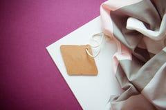 在绯红色背景的衣裳标签 图库摄影