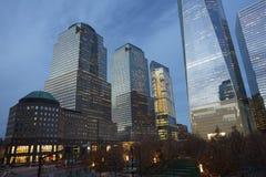 在9/11纪念品附近的区域有微明的毗邻摩天大楼的 免版税库存照片