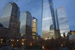 在9/11纪念品附近的区域有微明的毗邻摩天大楼的 免版税库存图片