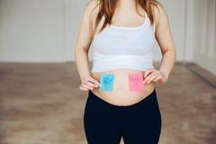 在贴纸的怀孕的腹部男孩和女孩图片,妇女期待婴孩的,家庭和育儿概念 怀孕的年轻人 免版税库存图片