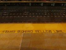 在黄线标志和tracs后站立爱迪生火车站晚上, NJ美国 免版税图库摄影