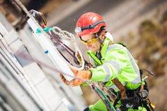 在绝缘材料工作期间的工业登山人 免版税图库摄影