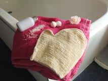 在浴缸的桃红色毛巾有浴手套的 库存照片