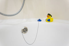 在浴缸边缘的黄色橡胶duckie  免版税库存图片