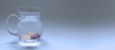 在水罐的水晶宝石精华水 免版税库存图片