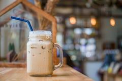 在水罐,在木桌面的杯子玻璃杯子的被冰的咖啡 免版税图库摄影