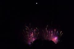 在紫罗兰色和红色烟的烟花在明亮的满月下 库存图片