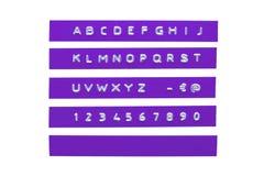 在紫罗兰色塑料磁带上的压印的字母表 图库摄影